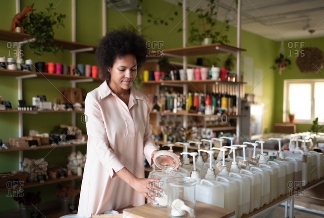 Ethnic woman choosing natural cosmetic in store