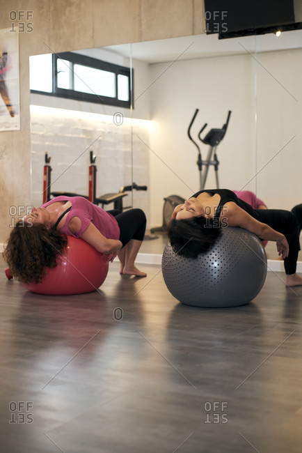 Two middle-aged women playing Pilates ball