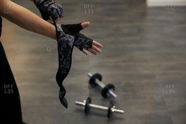 A woman putting on sports gloves for weight training