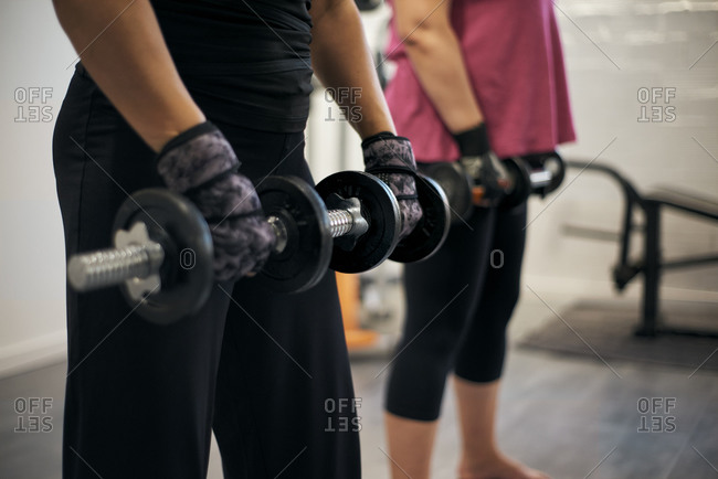 Two women are doing weight training at home