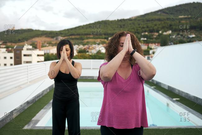 Women do yoga on the terrace of the house, namaste greeting