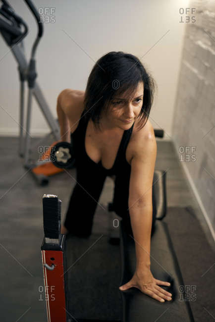 A middle-aged brunette woman doing weights on a bench at home