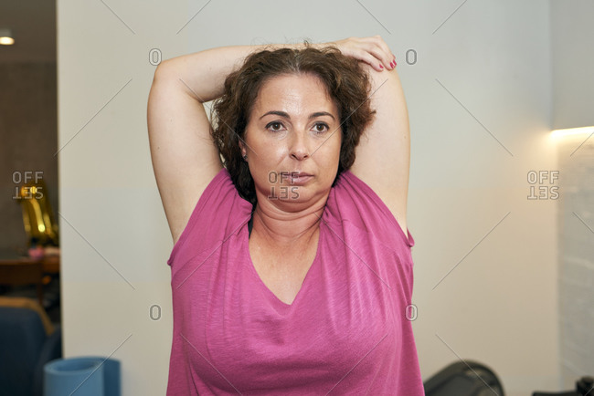 A middle-aged woman is doing stretching exercises at home