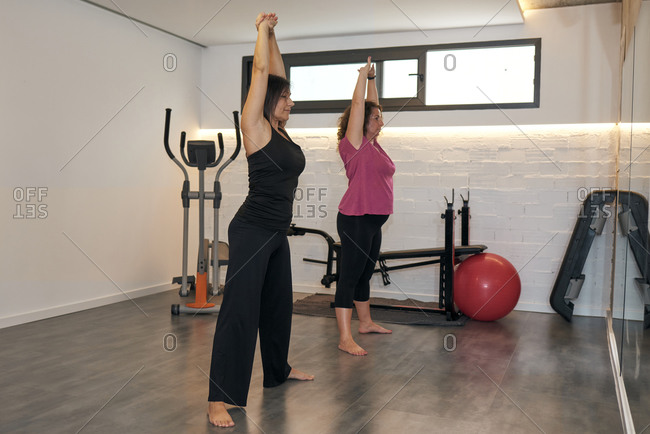 Two middle-aged women are doing stretching exercises at home