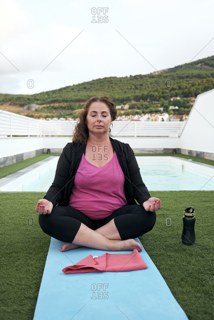 Woman practicing yoga on the terrace of the house, lotus posture