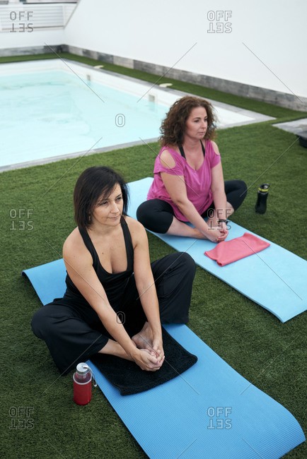 Two women practicing yoga on the terrace of the house, lotus posture