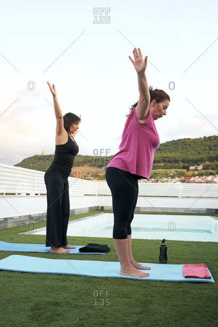 Two women practice yoga on the terrace of the open-air house