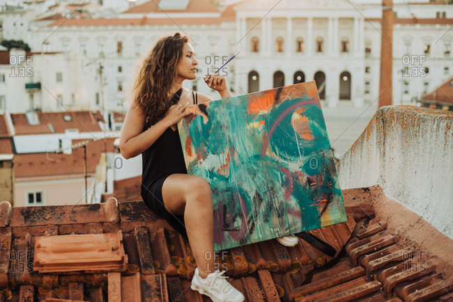 Female painter with abstract art canvas sitting on the roof in Lisbon