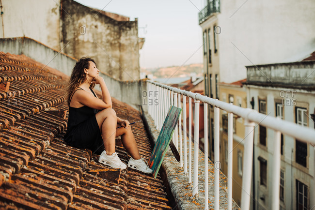 Female painter working on painting while sitting on tiled roof