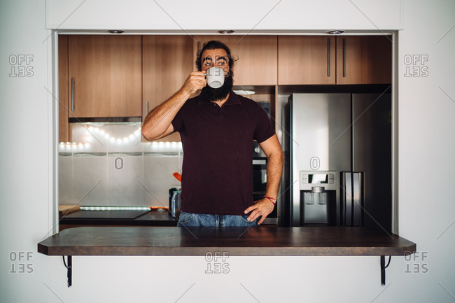 A bearded man framed on a kitchen bar drinking from a cup of coffee