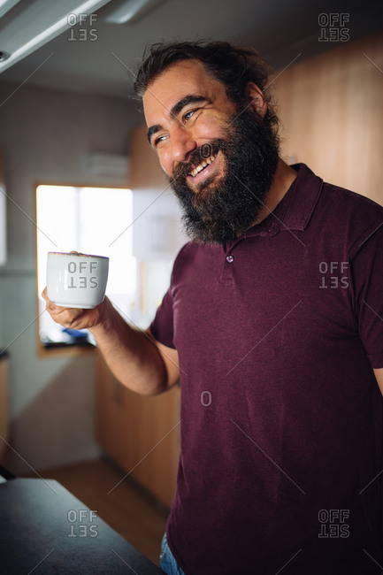 A bearded man smiles with his arm raised holding a cup of coffee