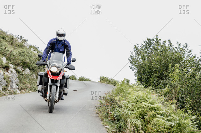 Motorcyclist driving on a road surrounded by vegetation in cloudy day