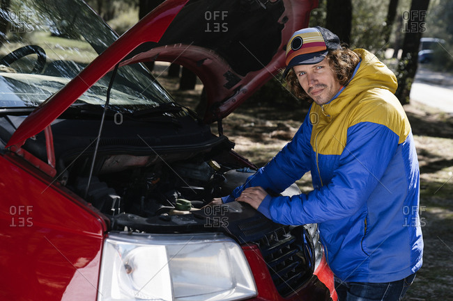 Man standing next to a Campervan open and fixing engine problems