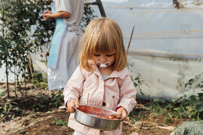 Little girl with a pacifier holding a casserole with cherry toma