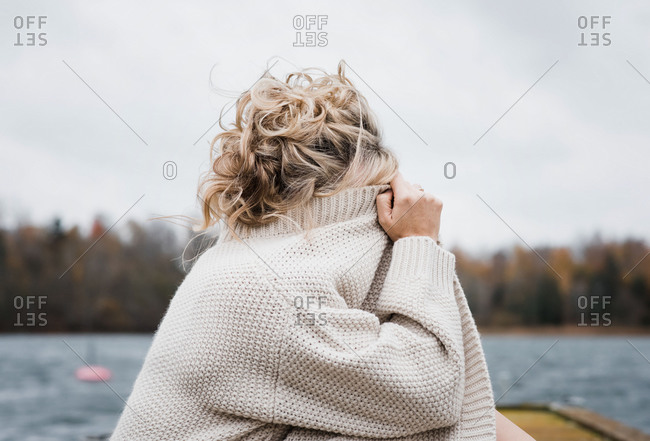 Woman sat outside covering her face with her cardigan