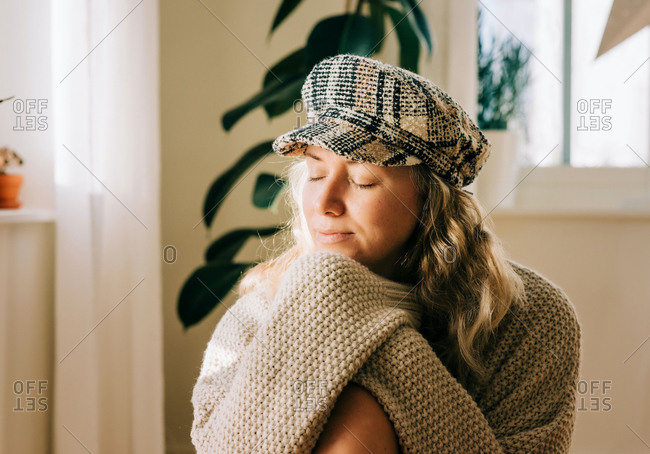Woman sat at home with her eyes closed enjoying the window sun