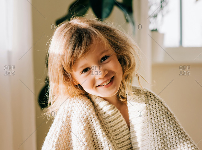 Portrait of a smiling young girl sat at home wrapped up in a blanket