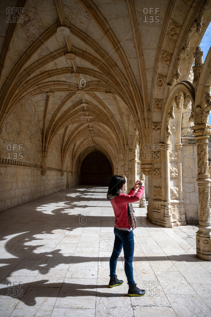 Traveler woman taking photo of an ancient building