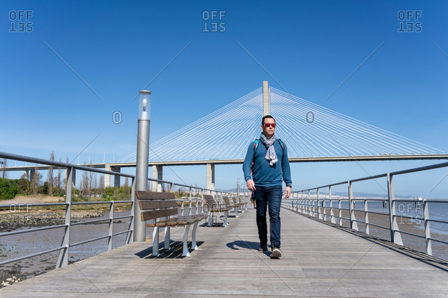 Tourist with backpack walking on a wooden pathway next to river