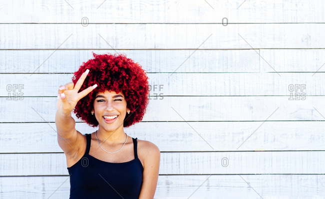 Portrait of woman with red afro showing victory symbol with fingers.