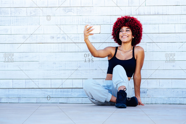 Woman with red afro hair taking a selfie with cellphone.