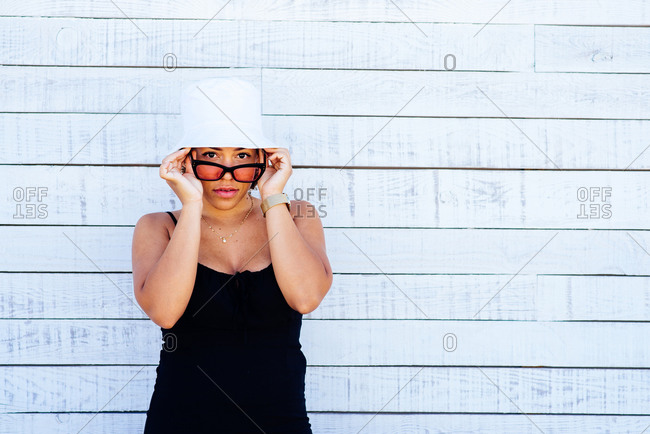 Woman wearing white hat and sunglasses standing on a white wall.