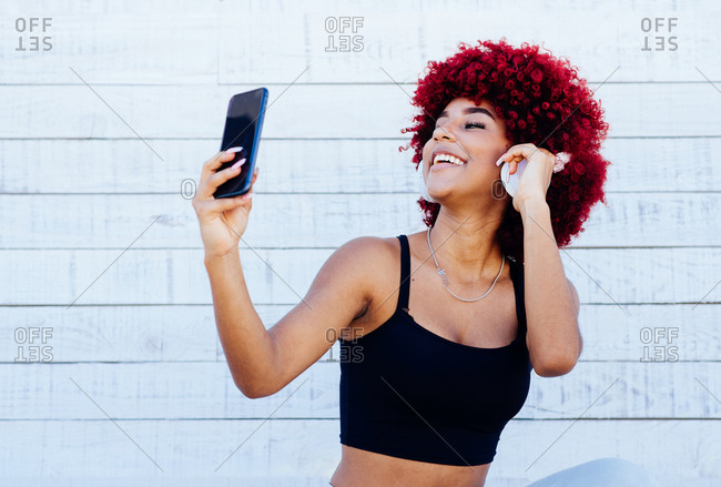 Woman with red afro hair listening music with headphones.