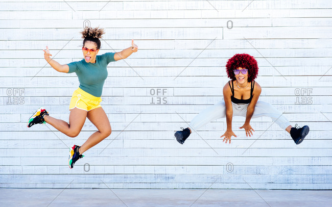 Two latin women with afro hair jumping and high five on white wall.