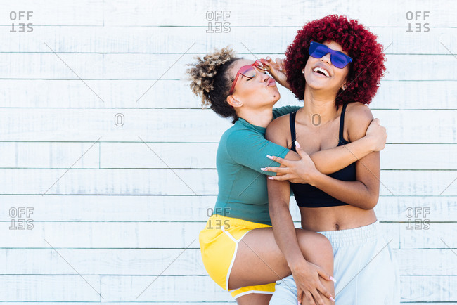 Two attractive latin girls with afro hair hugging each other amicably.