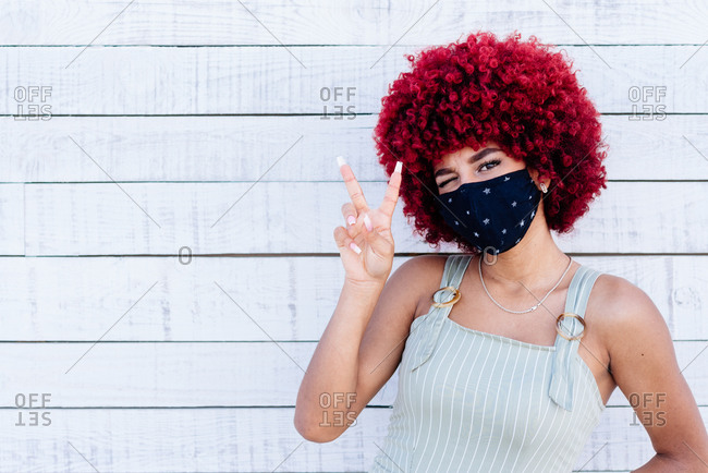 Latin women with mask and red hair showing a victory symbol.