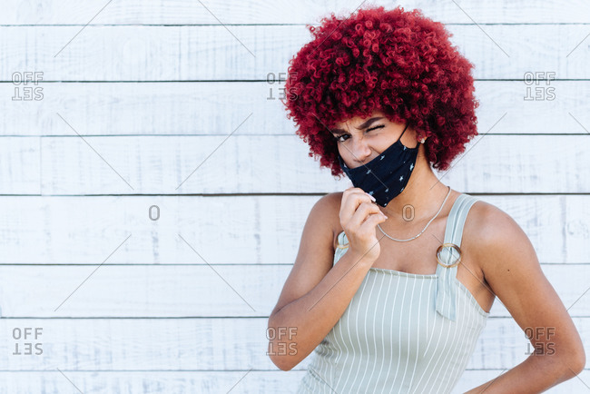 Latin woman with red afro hair and mask standing on a white wall.