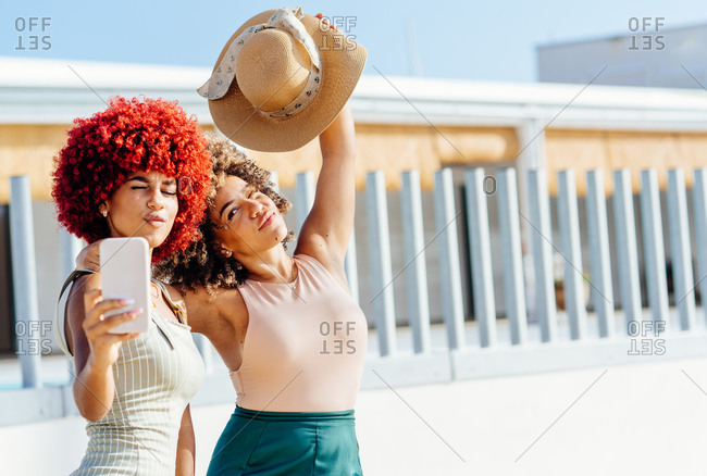 Two attractive latin girls with afro hair taking a selfie with phone.