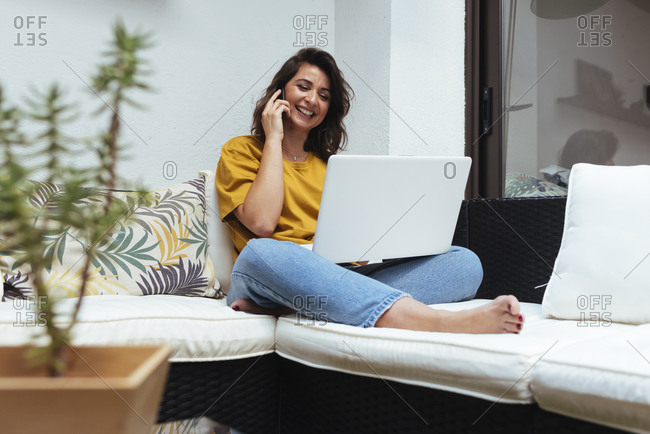 Woman talking on the phone while working with her laptop from home.