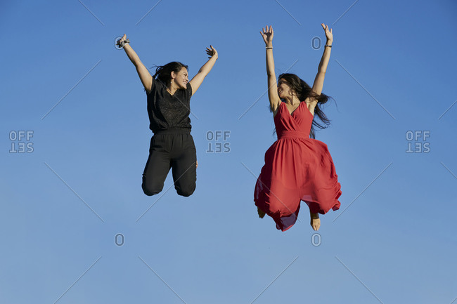 Young women couple smiling and jumping with blue sky in the background. summer concept