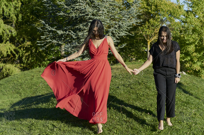 Young lesbian couple holding hands walking on green grass in a park on sunny day. romantic concept
