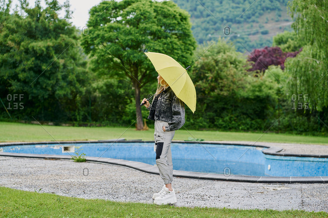 Young blonde braided hair woman wearing jean jacket sitting in an empty swimming pool with an umbrella. Fashion concept