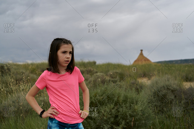 Girl wearing a pink blouse posing in the Bardenas Reales national park in Navarra, Spain. Tourism concept