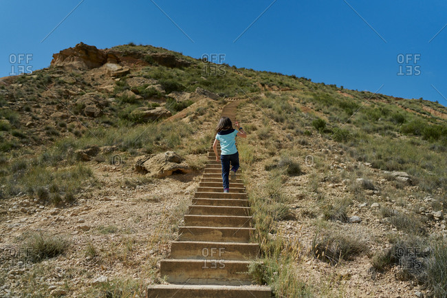 Girl climbing some stairs in the Bardenas Reales national park in Navarra, Spain. Travel concept