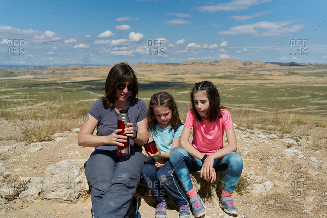 Mother and two daughters take a break and drink water in the Bardenas Reales desert in Spain