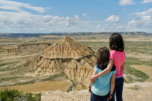 Little sisters in viewpoint observing a desert mountain in the Bardenas Reales national park in Navarra, Spain. Travel concept