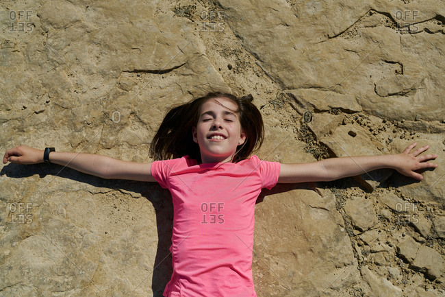 Girl wearing a pink blouse lying on a rock in the Bardenas Reales National Park in Navarra, Spain. Tourism concept