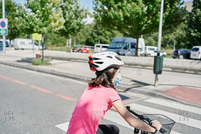 Girl riding bike on empty street in his neighborhood, wearing fa
