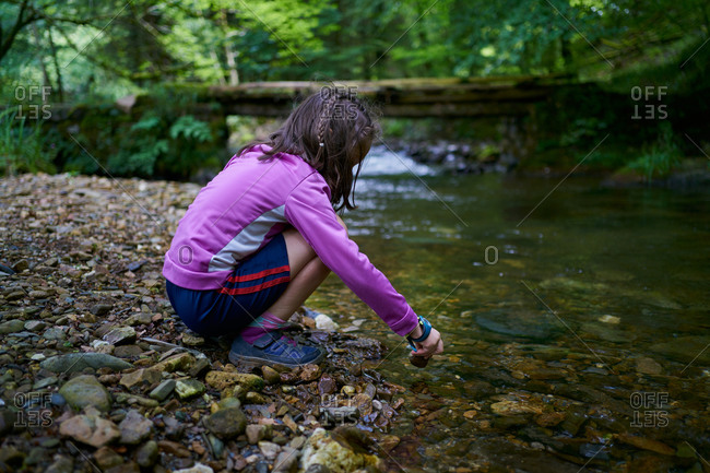 Girl bending over a river bank playing with water and stones