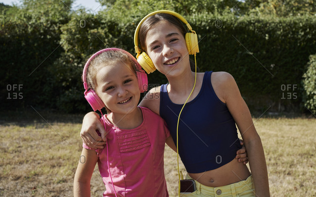 Little girls hugging and listening to music with yellow and pink headphones in the garden. Summer concept