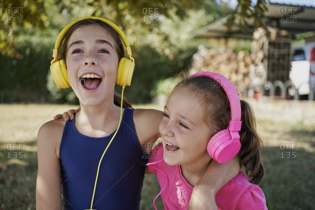 Little girls listening to music and singing with yellow and pink headphones in a garden. music concept