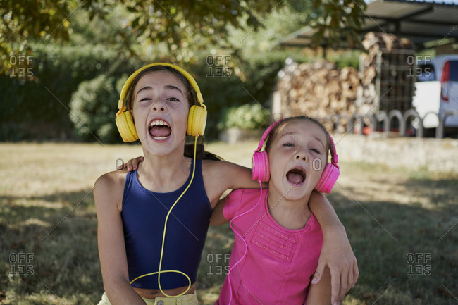 Little girls listening to music and smile with yellow and pink headphones in a garden. music concept