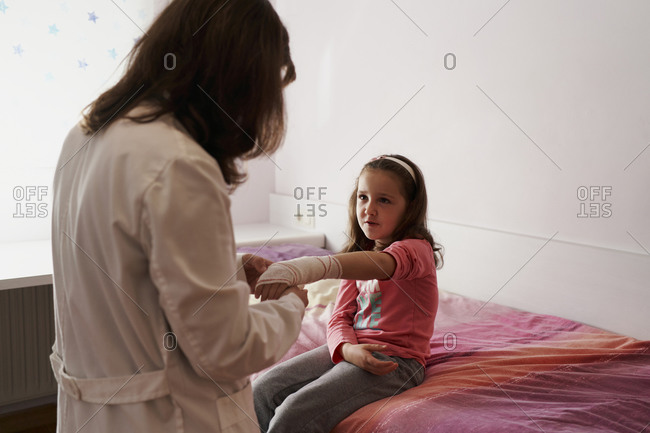 Side view of a female doctor bandaging the arm of a little girl in her room. Home doctor concept