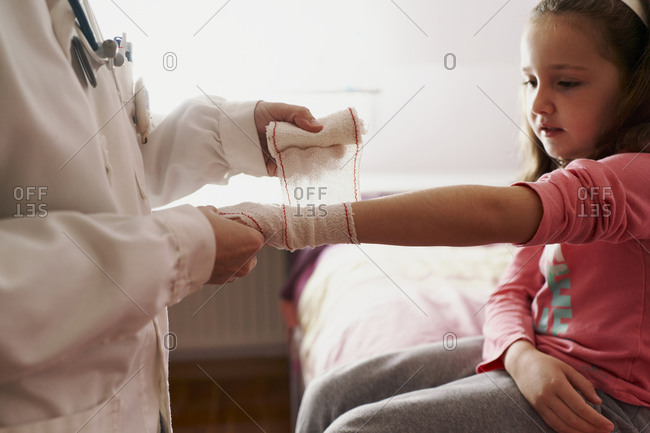 Female doctor bandaging the arm of a little girl in her room. Home doctor concept