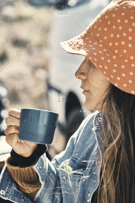 Close up portrait of woman drinking from a glass outdoors
