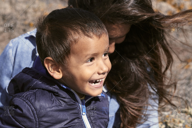 A little boy smiles sat with his mother